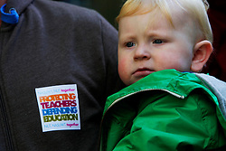 Licensed to London News Pictures 17/10/2013<br /> London. UK. <br /> A teacher on strike holds his son, Dylan Warring, 13 months, whilst joining a protest through central London against a government decision to not give teachers a pay rise. <br /> Photo credit: Anna Branthwaite/LNP