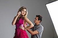 Female fashion model using cell phone while designer adjusting her dress in studio