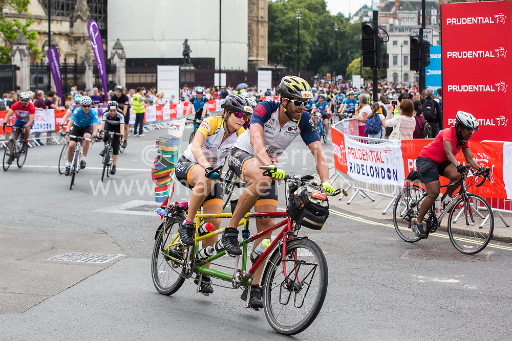 London, UK. 4 August, 2019. Riders from the Prudential RideLondon-Surrey 100 and 46 events cross Parliament Square on their way to the finish for both events in the Mall. Both events take place on traffic-free roads in London and Surrey, with the 100 event featuring leg-testing climbs on a route made famous by the London 2012 Olympics.