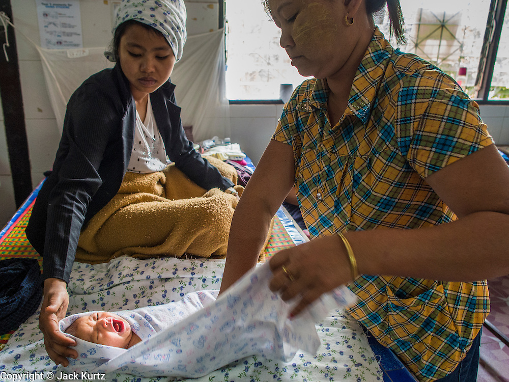 05 MARCH 2014 - MAE SOT, TAK, THAILAND: A health worker, right, helps a new mother swaddle her baby in the OB/Gyn ward at the Mae Tao Clinic. The Mae Tao Clinic provides  healthcare to over 150,000 displaced Burmese per year and is the leading healthcare provider for Burmese along the Thai-Myanmar border. Reforms in Myanmar have alllowed NGOs to operate in Myanmar, as a result many NGOs are shifting resources to operations to Myanmar, leaving Burmese migrants and refugees in Thailand vulnerable.     PHOTO BY JACK KURTZ