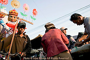 A toy salesman wearing a cap is working on a crowded city street in Phnom Penh, Cambodia.