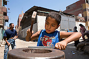 A young Boy prepares some aluminium to be worked on by hammering it on a steel anvil. Children often help their parents in working along side schoolwork.
