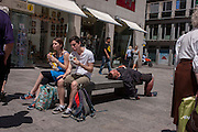 Surrounded by tourists, a man lies down on a street bench in Vienna, Austria, EU.