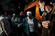 An injured protester is evacuated from a first aid post after  treatment during clashes with riot police on a side street near Tahrir Square on November 22, 2011 in Cairo, Egypt.