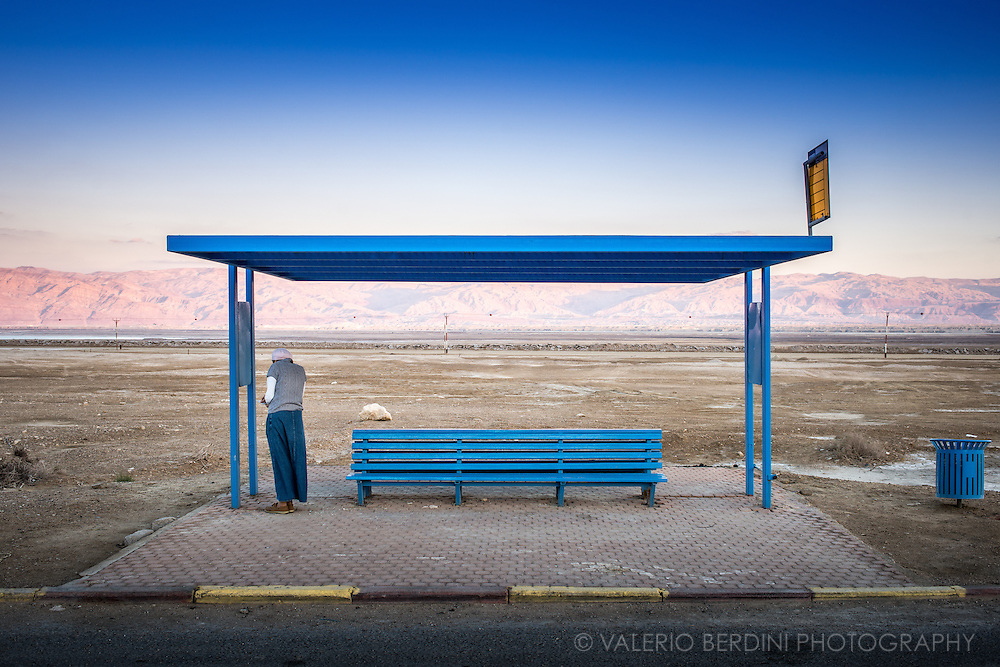 A Haredi Jewish woman got off her husband car at a bus stop next to Masada, in the southern Dead Sea region, and began praying silently holding a bible and waiting for the sunset.