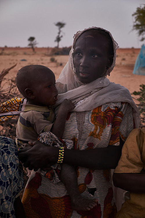 Amina Tijani holds her son at her shelter in a camp of internally displaced people by the side of the road on the highway outside of Diffa, Niger on February 11, 2015.<br /> <br /> 'I am from the village of Chilori in Niger, close to the border with Nigeria. We fled two months ago when the village was attacked by Boko Haram. Some old people stayed but the rest fled. They killed ten people. I have six children and we dont have anything, no water, clothes,e food, anything.'