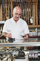 Mature male merchant at gun shop with credit card reader