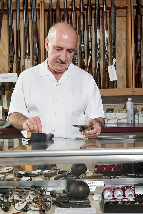 Mature male merchant at gun shop with credit card reader