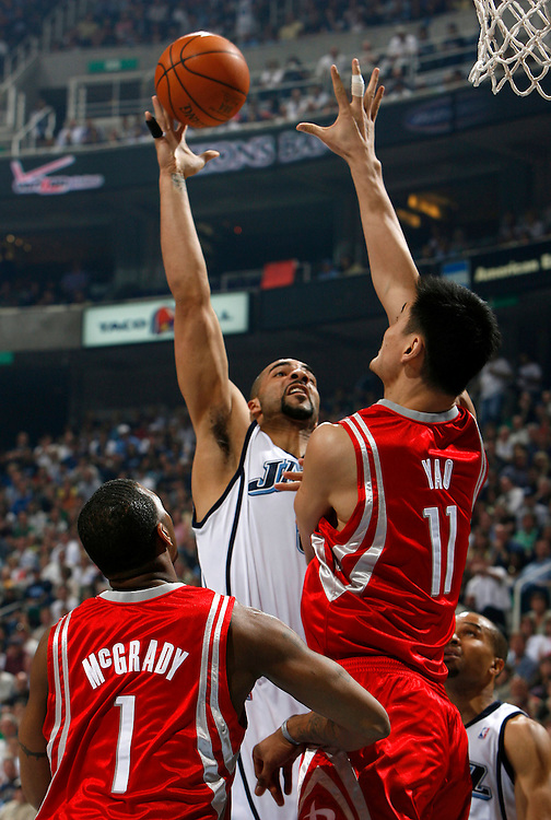 The Utah Jazz's Carlos Boozer goes up for two points over Yao Ming of the Houston Rockets as Tracy McGrady looks on in game 4 of the first round of the playoffs at the Energy Solutions Arena in Salt Lake City, Utah Saturday, April 28, 2007.  August Miller/ Deseret Morning News