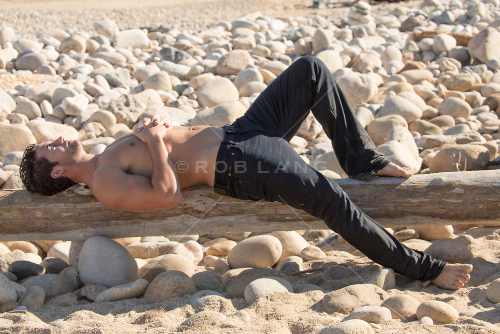 shirtless man resting on a log at the beach