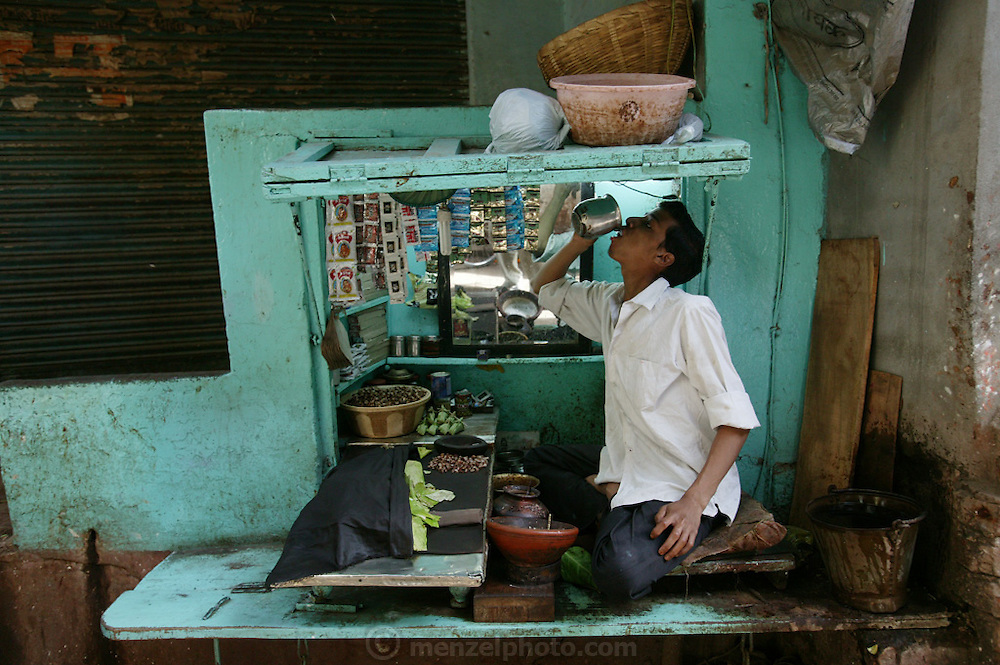 A betel nut vendor takes a drink of water between customers in Varanasi, India. Betel nut is a mildly narcotic seed eaten with lime paste and a green leaf. Over time it decays the teeth and dyes the mouth of the user red. Although its not considered a food, it is a plant item chewed by many all over Asia, and kept in the mouth like chewing tobacco. (From a photographic gallery of street images, in Hungry Planet: What the World Eats, p. 131).