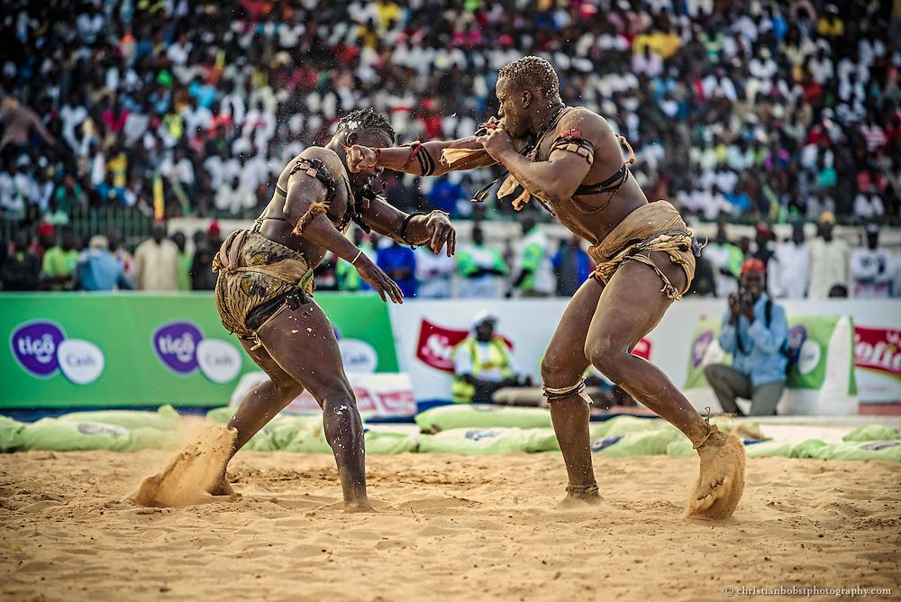 """Bei einem Kampf am 5. April 2015 im Stadion von Samba Diop  versetzt Modou Dia seinem Gegner Mame Balle einen Faustschlag ins Gesicht. Im Gegensatz zur """"lutte traditionelle"""" sind bei der """"lutte avec frappe"""" Boxhiebe erlaubt."""