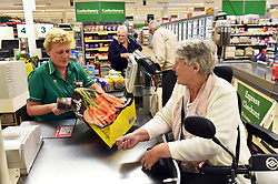 A shop assistant helps an elderly woman with her shopping at Morrisons supermarket checkout UK