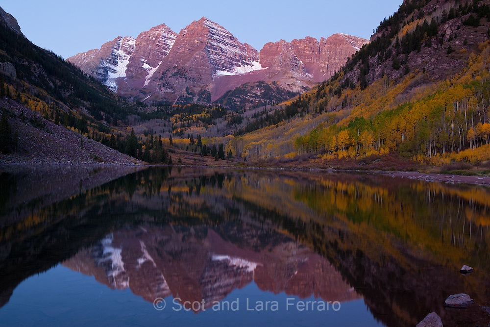 Maroon Bells reflected in Maroon Lake in predawn twilight.