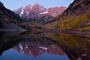 Maroon Bells reflected in Maroon Lake in predawn twilight.