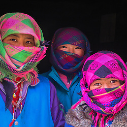Three girls smiling and protecting themselves with shawls agains the cold in Eastern Tibet, Tibet