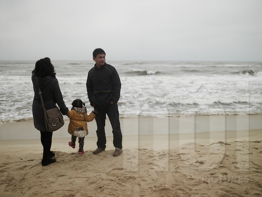 A family hang out on a beach by a winter cold day. They wore clothes very warm. Mother and daughter overlook the sea while the father is looking over the beach. Quang Binh province, viet nam, asia
