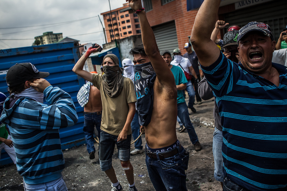 SAN CRISTOBAL, VENEZUELA: Men celebrate after pulling a shipping containter up a 100 yard incline to be used as a barrier in the Las Pilas area of San Cristobal. Las Pilas is one of the hardest hit areas of the protests in all of Venezuela. Anti-government protesters have taken to the streets, constructing barriers on nearly every block, completely gridlocking the city, to protest high inflation, high crime rates and shortages of basic goods, among other things. The protests in Venezuela began in San Cristobal, in the western state of Tachira, and are recognized as being the strongest in the country.   CREDIT: Meridith Kohut