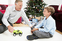 Grandfather playing with grandson on floor by christmas tree
