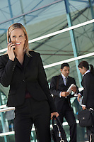 Businesswoman using mobile phone with coworkers in background