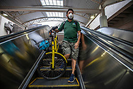 Andrew Cendan, 42, rides the escalator along with his bike as he commutes to work by Metrorail while wearing a protective mask during the COVID19 pandemic in downtown Miami on Wednesday, April 1, 2020.