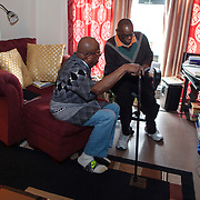 Mr. Johnson, left, and his caretaker Reggie Griffin look over Mr. Johnson's checkbook and bank balance. John E. Johnson, who is not eligible for medicaid, receives services for 12 hours per week through Illinois&rsquo; Community Care Program. Johnson worries his services will be cut if the state transition seniors like him to a new program. The state employs Reggie Griffin to help Johnson with daily chores so he is able to stay in his home, as opposed to going to an nursing home. <br /> Photography by Jose More