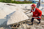 "28 MARCH 2014 - NA KHOK, SAMUT SAKHON, THAILAND: A worker stacks salt on a drying area in Samut Sakhon province. Thai salt farmers south of Bangkok are experiencing a better than usual year this year because of the drought gripping Thailand. Some salt farmers say they could get an extra month of salt collection out of their fields because it has rained so little through the current dry season. Salt is normally collected from late February through May. Fields are flooded with sea water and salt is collected as the water evaporates. Last year, the salt season was shortened by more than a month because of unseasonable rains. The Thai government has warned farmers and consumers that 2014 may be a record dry year because an expected ""El Nino"" weather pattern will block rain in mainland Southeast Asia. Salt has traditionally been harvested in tidal basins along the coast southwest of Bangkok but industrial development in the area has reduced the amount of land available for commercial salt production and now salt is mainly harvested in a small parts of Samut Songkhram and Samut Sakhon provinces.    PHOTO BY JACK KURTZ"