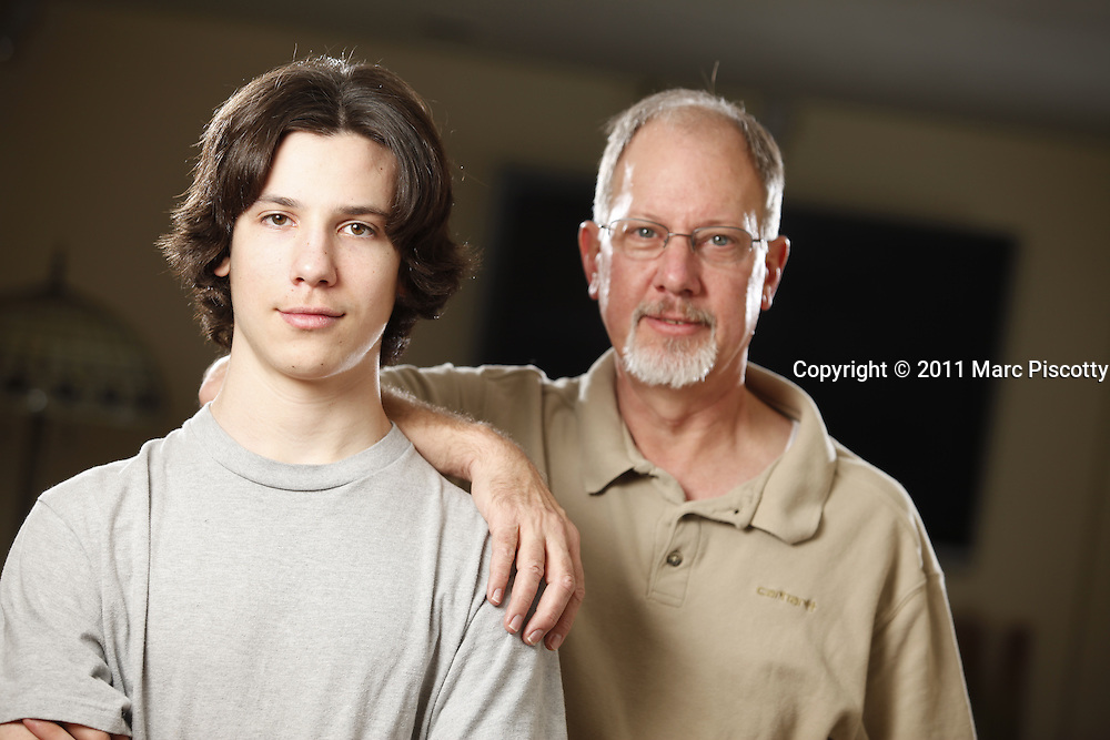 """SHOT 2/5/11 12:12:22 PM - Michael Enright and his 14 year-old son Hunter, who has Type 1 diabetes pose for a portrait at their Golden, Co. home one weekend. Michael is president of AAA Service Plumbing, Heating and Electric in Arvada and insures some 60 employees and their families through his company. He is pragmatic about the healthcare debate and doesn't believe there should ever be any lifetime cap on benefits and added, """"there seems to be a lot of other countries doing it (healthcare) better than we are here. We're definitely not getting our money's worth out of it right now."""" Hunter is a freshman at Golden High School and discovered he had diabetes when he was 11 years old. (Photo by Marc Piscotty / © 2011)"""