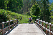 Cyclist crosses a wooden bridge over the Inn river at Scuol in the Swiss canton of Grisons
