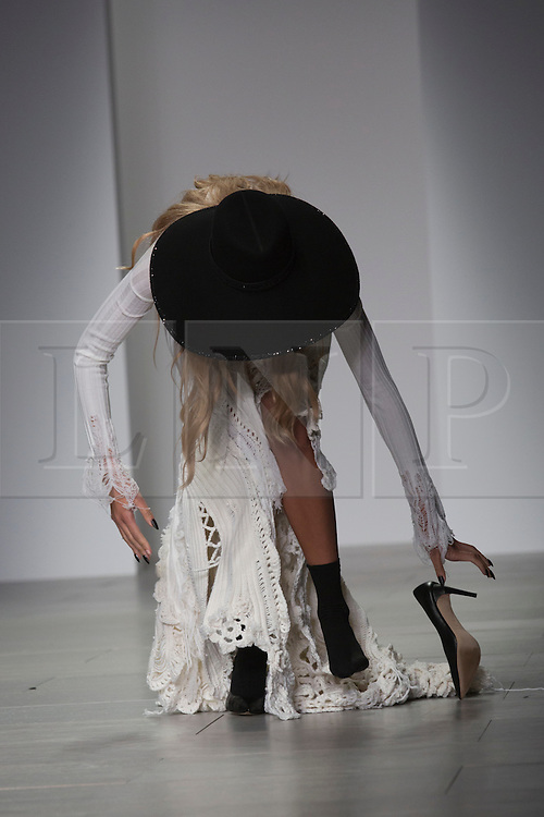 © Licensed to London News Pictures. 15 February 2014, London, England, UK. A model's shoe gets entangled in a knitwear dress and she finally discards her shoes. A model walks the runway at the Sister by Sibling show during London Fashion Week AW14 at Somerset House. Photo credit: Bettina Strenske/LNP