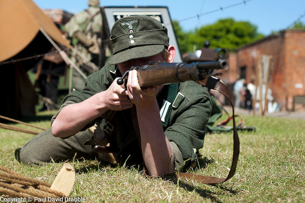 A world War two German Soldier wearing an M43 Ski Cap in the prone firing position using a Mauser K98 bolt action rifle May 2011 <br /> Image &copy; Paul David Drabble