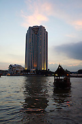Chao Praya River. Sunset view from terrace of Oriental Hotel. Peninsula Hotel in background.
