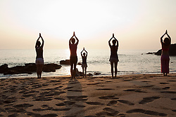 Jul. 25, 2012 - Women practicing yoga on beach at sunset (Credit Image: © Image Source/ZUMAPRESS.com)