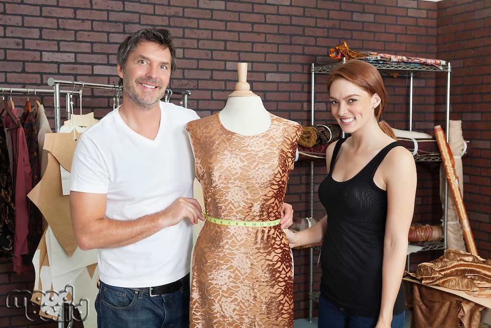 Portrait of fashion designers working together on an outfit in design studio