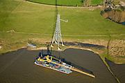 Nederland, Gelderland, Bommelerwaard, 11-02-2008; hoogspanningsmast vlakbij het plaatsje Heesselt aan de oever van de rivier de Waal (tegenover Hurwenen); in december 2007 is hier een Apache-gevechtshelikopter tegen de hoogsapnningskabel gevlogen, de mast is drie maanden later slechts gedeeltelijk hersteld. Continuon, de netbeheerder van elektriciteitsbedrijf NUON, heeft een schadeclaim bij het ministerie van defensie ingediend; Tielerwaard, energie, elektriciteit, electriciteit, hoogspanning, koppelnet, hoogspanningsmast, hoogspanningsdraden, stroom,  energievoorziening; ongeluk, ongeval, helicopter, apache..luchtfoto (toeslag); aerial photo (additional fee required); .foto Siebe Swart / photo Siebe Swart
