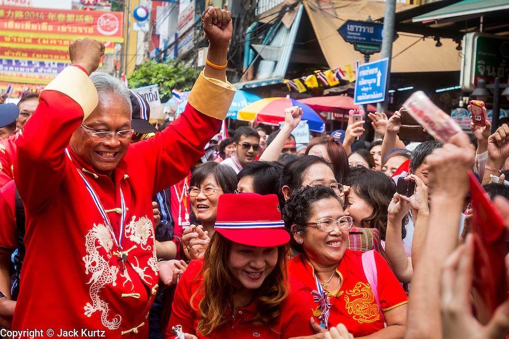 01 FEBRUARY 2014 - BANGKOK, THAILAND: SUTHEP THAUGSUBAN walks through Chinatown in Bangkok. The anti-government protest movement, led by the People's Democratic Reform Committee (PDRC) organized a march through the Chinatown district of Bangkok Saturday and disrupted the city's famous Chinese New Year festival. Some streets were blocked and Suthep walked through the neighborhood collecting money. Suthep and other protestors wore red Saturday in honor of Chinese New Year. Normally the anti-government protestors wear yellow (the color of the King) or anything but red, which is the color worn by the Red Shirts. The march was in advance of massive protests the PDRC has promised for Sunday, Feb. 2 in an effort to block Thais from voting in the national election.     PHOTO BY JACK KURTZ