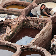Worker in dye vat at Chouara Tannery in Fes Morroco