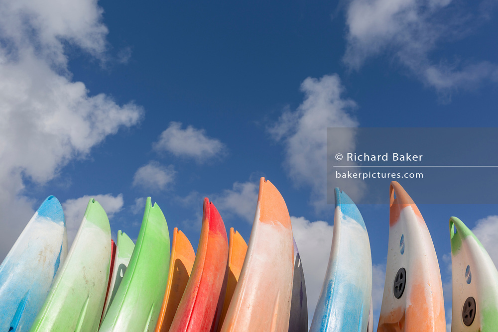 After heavy use during a busy summer, canoes are stacked vertically under still clear skies, on 12th September 2018, in Aberdovey, Gwynedd, Wales.