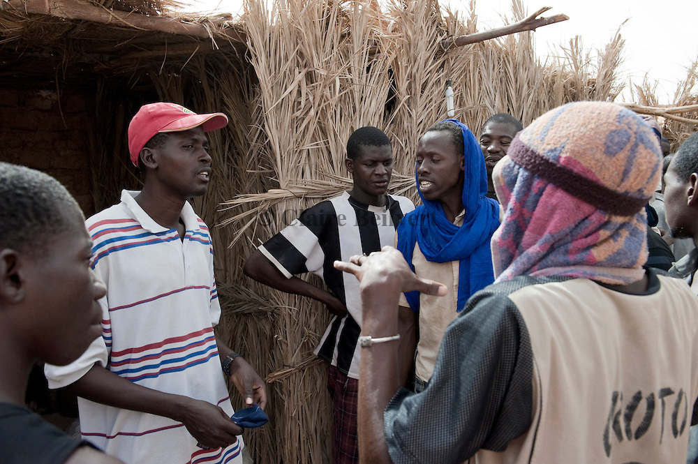 Ousmane ( red cap ) having some kind of argument with Oumaru and other African migrants from Burkina Faso in a ghetto in Dirkou.