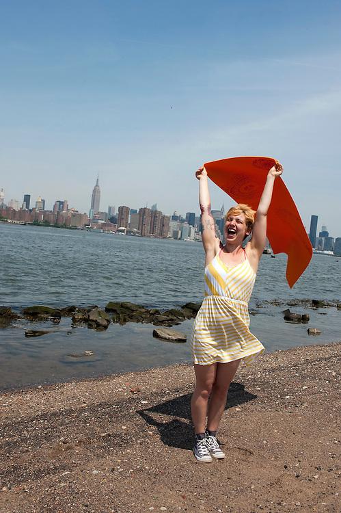 Yvonne Adamek mit Yoga Matte am East River in Williamsburg, Brooklyn, mit Sicht auf Manhattan's Skyline..Yoga in New York..Foto: Stefan Falke