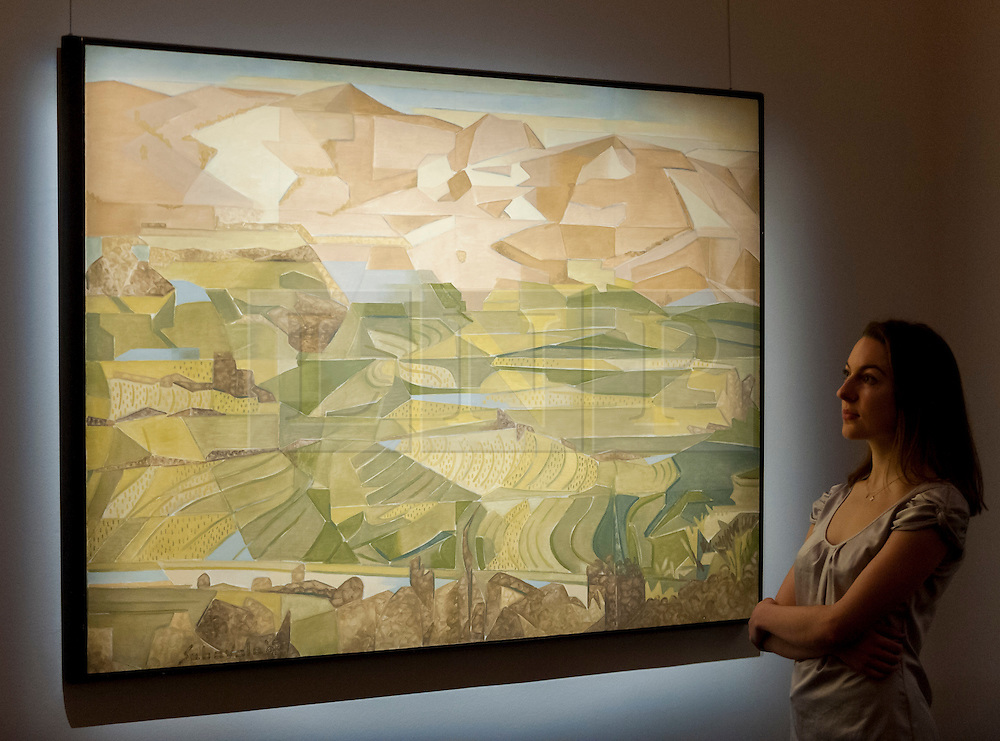 "© Licensed to London News Pictures. 13/10/2016. London, UK. A Sotheby's staff member views ""Rice Fields, Palni Hills - II, 2008"" by Jehangir Sabavala (est. GBP 160-180k) at the preview of Sotheby's Art of the Middle East and India exhibition, which presents artworks to be sold in New Bond Street in four sales in October. Photo credit : Stephen Chung/LNP"