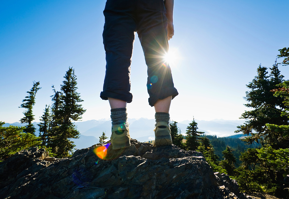 Low angle wide angle view of womans legs and shoes standing on top of a rocky outcrop on Hurricane Ridge in Olympic National Park, Washington