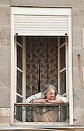 Granville Carnival, Normandy, France. Pictured here, a woman watches the main procession from her window, on the last Sunday before Lent. The carnival in Granville is the largest in Normandy, drawing some 120,000 people to this small town on the coast with a population of just 10,000, and has been running for 141 years (15 February 2015). © Rudolf Abraham