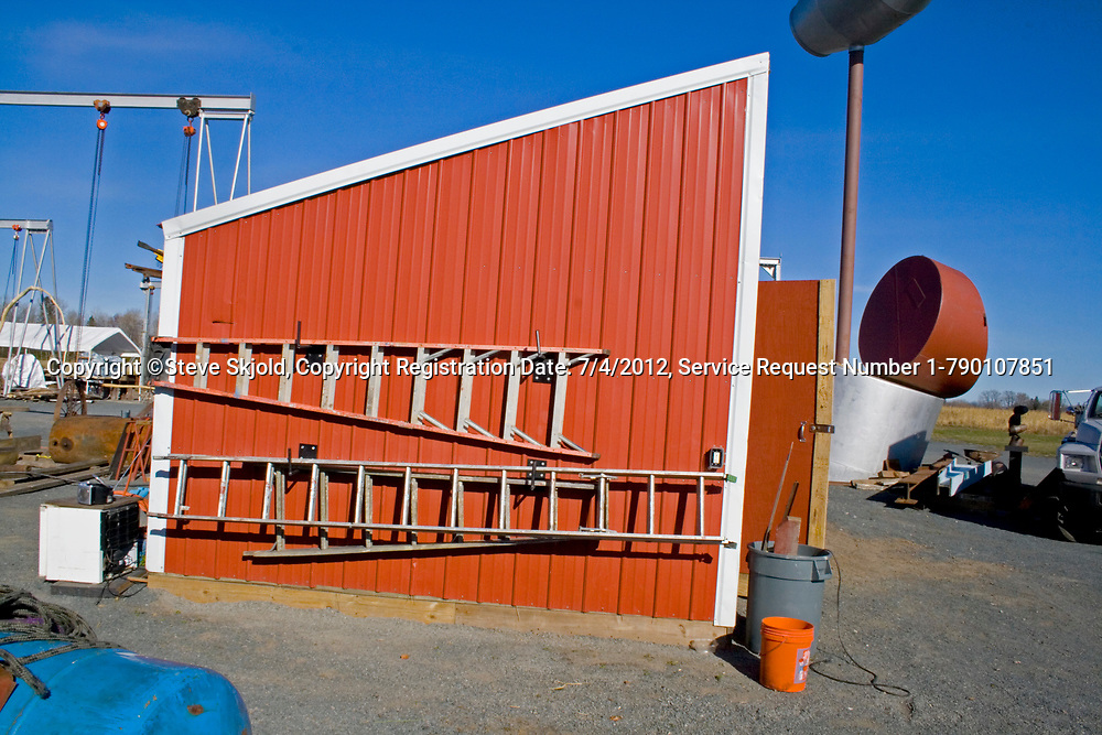 Bright red utility shed with slanted roof and ladders hanging on the side. Franconia Sculpture Park Franconia Minnesota MN USA