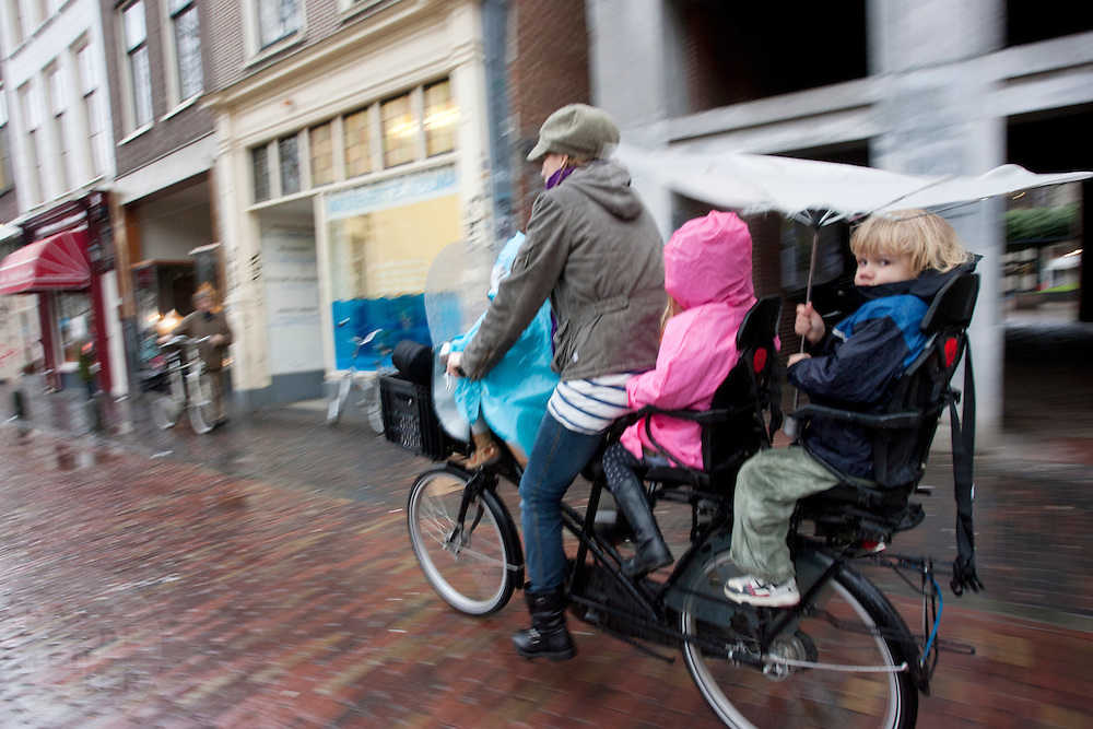 Een moeder fietst met drie kinderen op de fiets door de regen.<br /> <br /> A mother is cycling with three kids on a bike in the rain