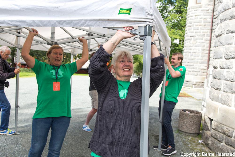 Frivillig vertskap må også arbeide med rigg i blant. Eva Larssen (foran) leder teamet som rigger telt utenfor Lademoen kirke.