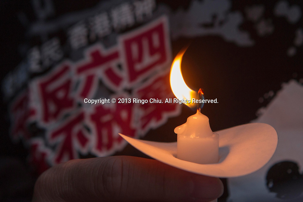 A protestor holds a candle during a candlelight vigil for the 24th anniversary of June 4 Tiananmen Square Massacre in Beijing at outside of The Consulate General of the PRC on June 4, 2013 in Los Angeles.  (Photo by Ringo Chiu/PHOTOFORMULA.com)