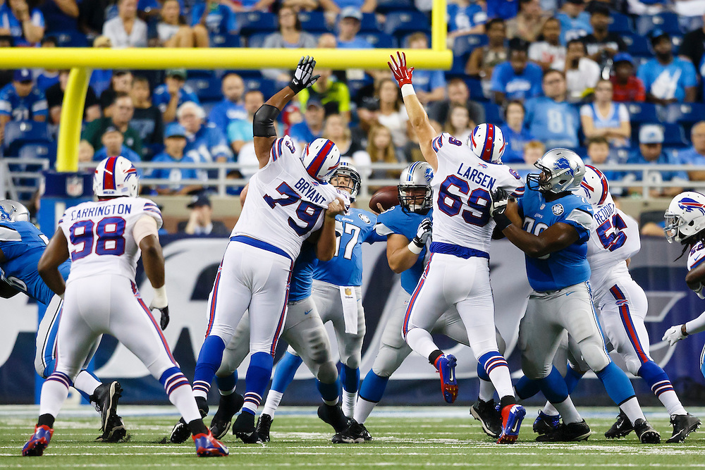 Buffalo Bills defensive tackle Red Bryant (79) and defensive end B.J. Larsen (69) pressure Detroit Lions quarterback Kellen Moore (17) during an preseason NFL football game at Ford Field in Detroit, Thursday, Sept. 3, 2015. (AP Photo/Rick Osentoski)