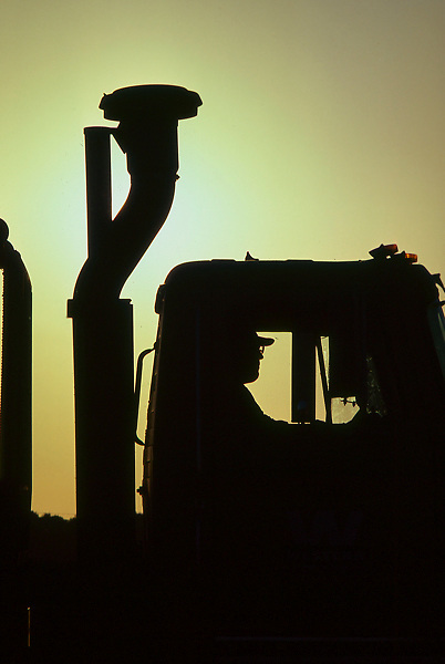 An oilfield truck and driver sillhouetted at sunset.