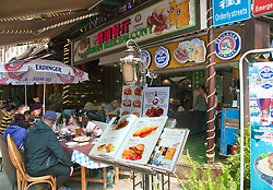 Restaurant and street scene, West Street, Yangshou. Yangshuo is a county and city under the jurisdiction of Guilin City, in the northeast of Guangxi Province, China. Its seat is located in Yangshuo Town. Surrounded by karst peaks and bordered on one side by the Li River it is easily accessible by bus or by boat from nearby Guilin. It is a major tourist and resort destination for Chinese and foreigners alike.